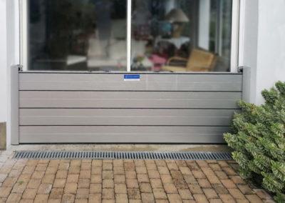 batardeau à glissière protège une porte de garage